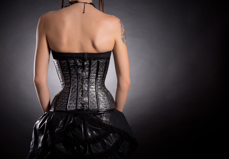 Back view of woman in silver leather corset with stars pattern, copy-space for your text