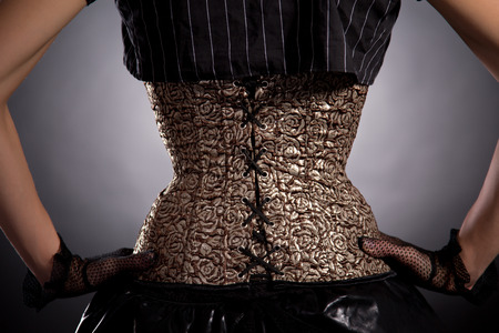 woman back view: Back view of woman wearing golden corset with floral pattern, studio shot on black background
