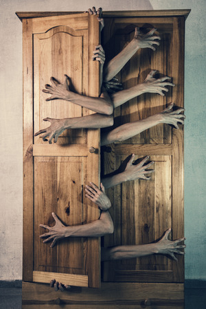 possessed: Monster with a lot of hands trying to escape from old grungy cupboard, Halloween theme