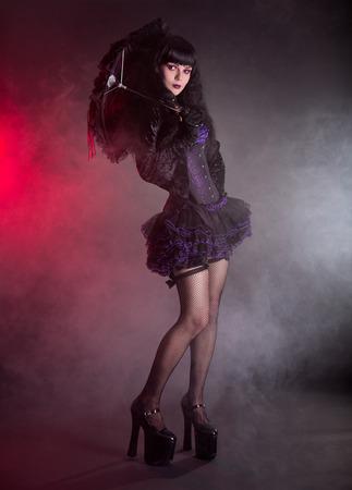 velvet dress: Gothic Lolita girl with lace umbrella, studio shot on black background  Stock Photo