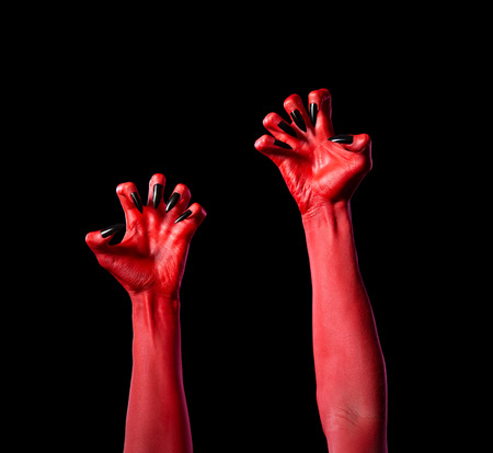 diabolic: Red devil hands with black nails, Halloween theme, isolated on black background