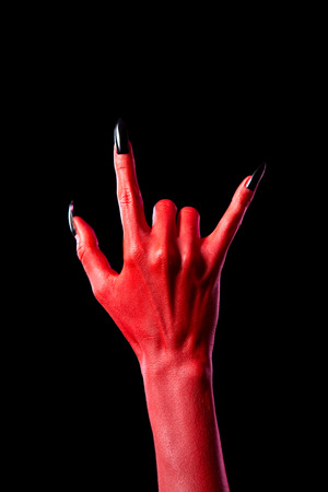 red devil: Devil hand showing heavy metal gesture, isolated on black background