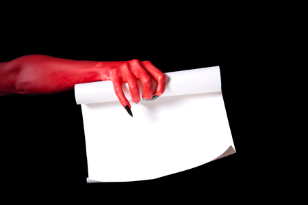 satan: Red devil hand holding paper scroll, Halloween deal with devil concept Stock Photo