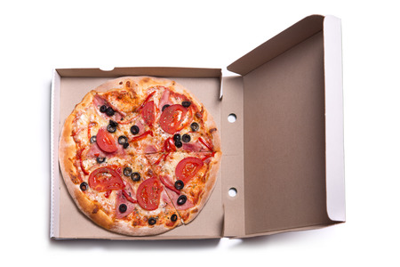 Delicious pizza with ham and tomatoes in box, isolated on white background