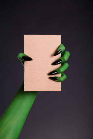 Green monster hand with black nails holding blank piece of cardboard, Halloween theme photo