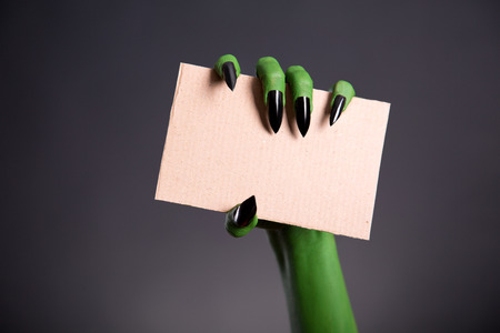 Green monster hand with sharp nails holding blank piece of cardboard, Halloween theme photo