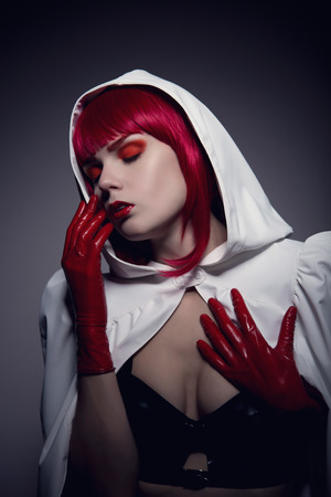 Mysterious sensual vampire girl with red lips wearing white hooded jacket, artistic shot photo