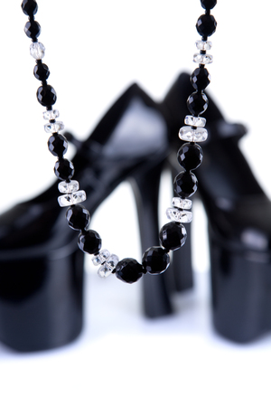 Pair of black platform shoes with necklace, selective focus on necklace photo
