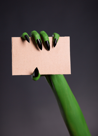 Green skin hand with sharp nails holding empty piece of cardboard, Halloween theme photo