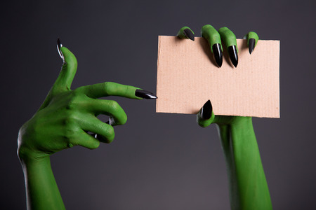 cardboard background: Green monster hand with black nails pointing on blank piece of cardboard, Halloween theme Stock Photo