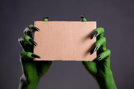 Green hands with black nails holding empty piece of cardboard, Halloween theme Standard-Bild