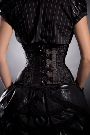 Rear view of young woman wearing elegant black corset, studio shot photo