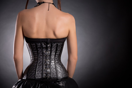 Rear view of gothic girl in silver leather corset with stars pattern, copy-space for your text Stock Photo