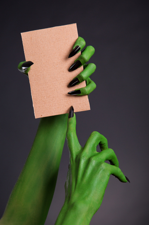 Green monster hands with black nails holding blank piece of cardboard, Halloween theme photo