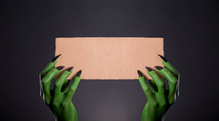 Green monster hands with black nails holding empty piece of cardboard, Halloween theme photo