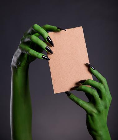 monster hand: Green monster hands holding empty piece of cardboard, Halloween theme