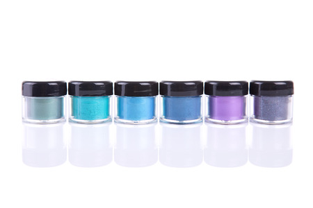 Mineral eye shadows in clear plastic jars, isolated on white background with natural reflection photo