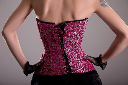 Rear view of elegant woman wearing purple corset with floral pattern Stock Photo