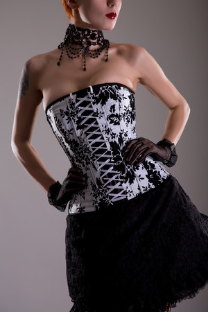 Attractive young woman in black and white corset with floral pattern, studio shot photo