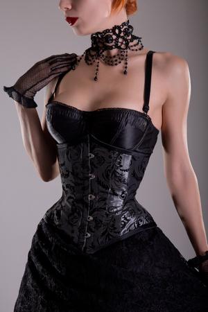 Beautiful gothic girl in silver corset and black skirt, studio shot photo