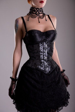 Attractive young woman in silver corset and black skirt, studio shot photo
