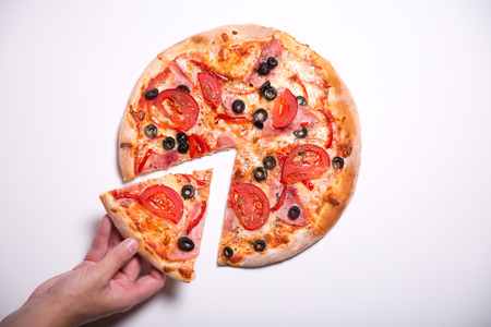high calorie foods: Male hand picking tasty pizza slice, studio shot on white background