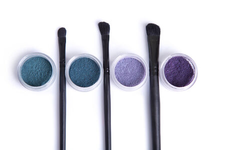 Top view of mineral eye shadows in pastel colors and brushes, isolated on white background photo