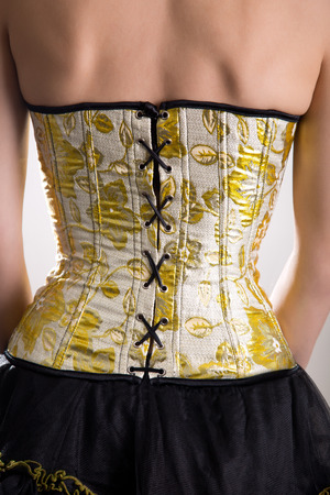 lacing: Rear view of beautiful woman in golden corset with floral pattern