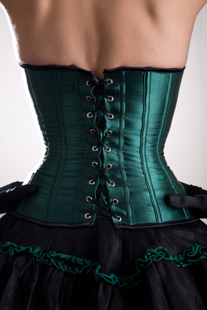 goth: Rear view of attractive woman in green corset, studio shot Stock Photo