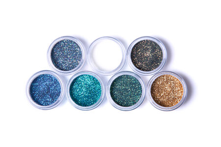 Two rows of metallic glitters in jars, top view isolated on white background Stock Photo