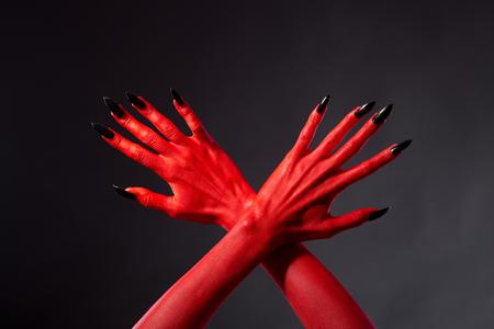 red devil: Crossed red devil hands with black nails, studio shot on black background