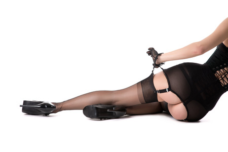 Sexy young woman in vintage girdle, corset, stockings and high heels, isolated on white background