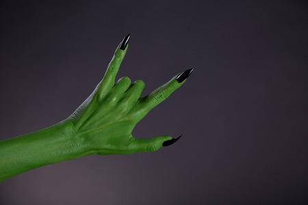 monster hand: Green monster hand showing heavy metal gesture, studio shot on black background
