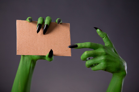 Green monster hands with black long nails pointing on blank piece of cardboard, Halloween theme photo