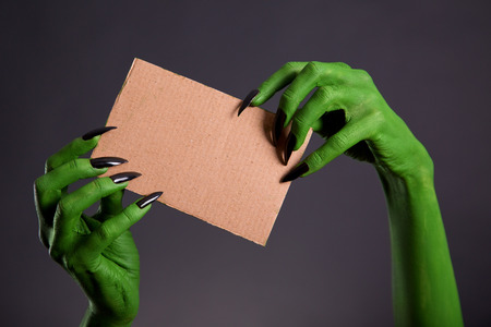 Green hands with long black nails holding empty piece of cardboard, Halloween theme   photo