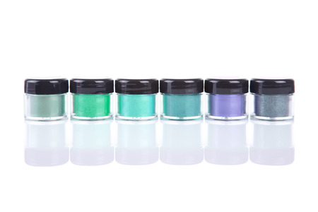 Row of green mineral eye shadows in clear plastic jars, isolated on white background