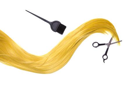 tijeras: Largo pelo rubio de oro con unas tijeras profesionales y cepillo de tinte para el cabello, aislado en fondo blanco Foto de archivo