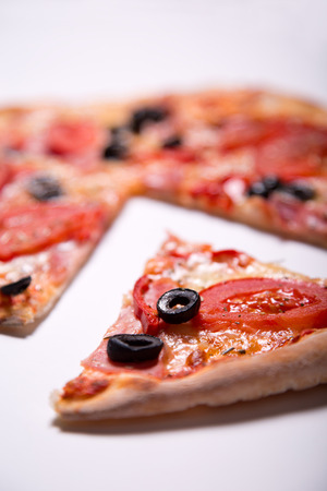 removed: Italian pizza with ham, tomatoes and olives with a slice removed, selective focus on slice