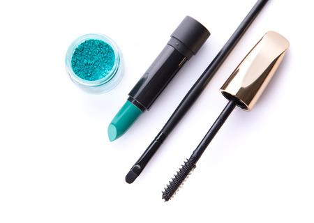 Bovenaanzicht van losse oogschaduw, lippenstift, make-up borstel en mascara, geïsoleerd op een witte achtergrond