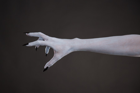 halloween background: Scary pale skin hand with black nails, body art for Halloween
