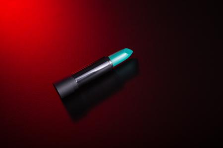 green lipstick: Teal green lipstick on red background, studio shot