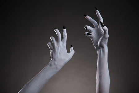 diabolic: Spooky Halloween white hands with black nails stretching up, body art