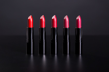 lapiz labial: Conjunto de barras de labios brillantes en tonos de color rojo, foto de estudio sobre fondo negro
