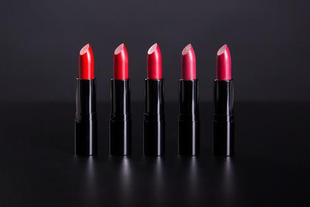 Set van heldere lippenstiften in de kleuren van de rode kleur, studio geschoten op zwarte achtergrond