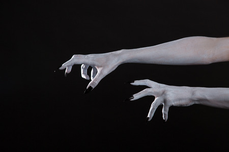 satan: Scary Halloween de manos blancas con las uñas negras, arte corporal Foto de archivo
