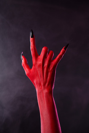 red hand: Scary devilish hand showing heavy metal gesture, studio shot on smoky background