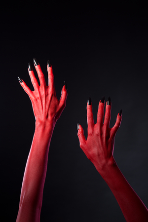 bodyart: Red devilish hands with black nails, Halloween theme, studio shot on black background