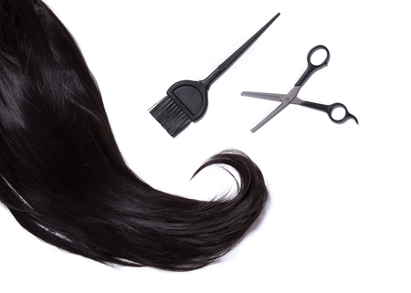 strand of hair: Top view on black shiny hair, hair dye brush, and professional scissors, isolated on white background