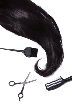 silky hair: Black silky hair, hair dye brush, scissors, and hairbrush, isolated on white background
