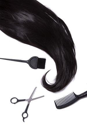 strand of hair: Black silky hair, hair dye brush, scissors, and hairbrush, isolated on white background